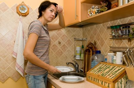 The tired woman washes tableware   without dishwasher Stock Photo