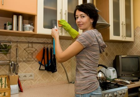 house chores: Young woman in gloves cleans a kitchen Stock Photo