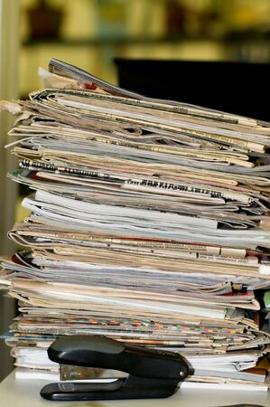 Heap of newspapers and magazines is in an office, disorder on a table. Stock Photo - 5937933