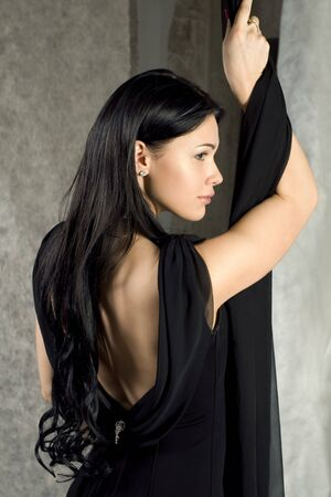 bared:  Beautiful woman in a black dress with the bared back