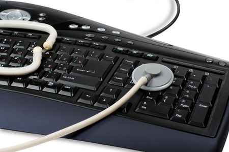 Computer keyboard and stethoscope is isolated on a white background