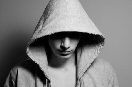hoodlum: The young guy in a hood and a shade in the face of.