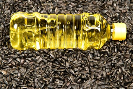 sunflowerseed:  Plastic bottle with sunflower-seed oil against sunflower seeds.