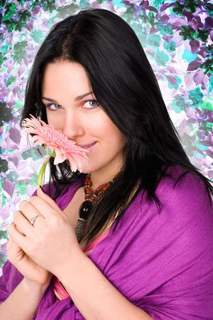 The beautiful, young woman with a gerberas in a hand against spring flowers. photo