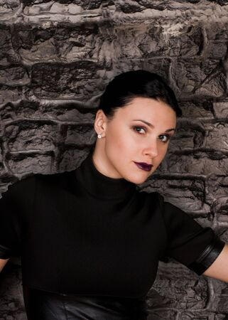 Beautiful girl in black clothes in style goth against a stone wall photo