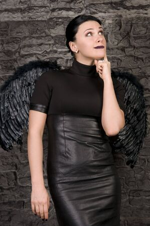 beautiful woman in the form of a black angel with wings against a stone wall. photo