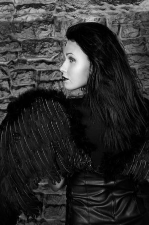 The beautiful woman with black wings against a brick wall. Demon of dark desires. photo