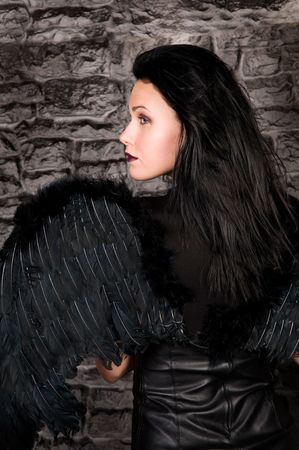 The beautiful woman with black wings against a brick wall. photo