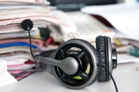 Headphones with a microphone and a mess on the table Stock Photo - 6796507