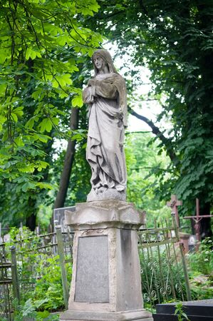 Sculpture of the woman on a tomb of the old, thrown cemetery. photo