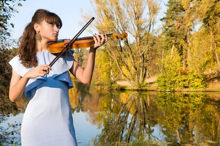 The young woman with a violin listens to music of autumn photo