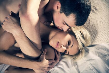 Young couple hugging on the bed in bedroom