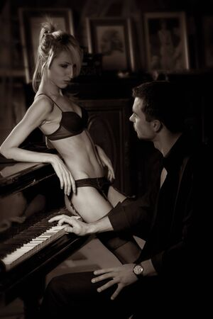 The musician plays the old piano, nearby the seductive woman photo