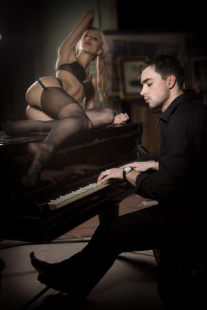 The musician plays the old piano nearby the seductive woman photo