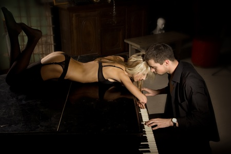 The musician plays the old piano nearby the seductive woman Stock Photo - 8569803