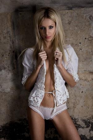 panties: Hermosa mujer en lencer�a blanca cerca de un muro de hormig�n Foto de archivo