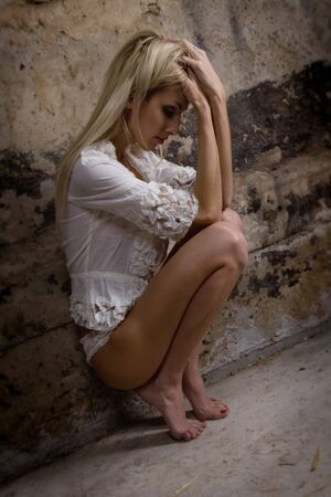 blonde underwear: Beautiful woman in a depression near a concrete wall Stock Photo