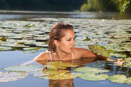 Beautiful young woman in a white bathing in the river photo