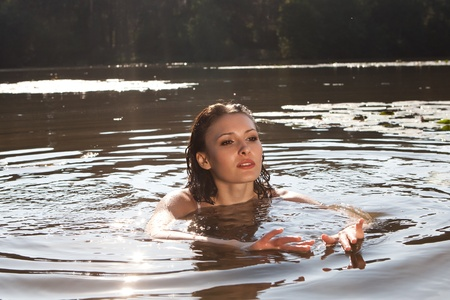 Beautiful young woman in the river photo