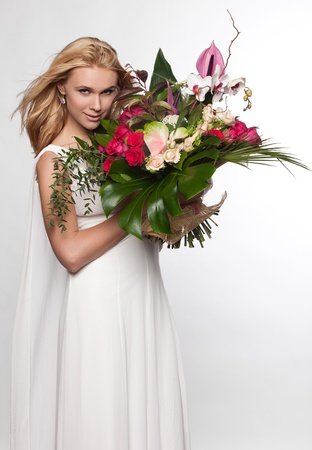 Woman in a white dress with flowers in their hands photo
