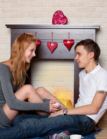 Young couple sitting by the fireplace in the st. Valentines day photo