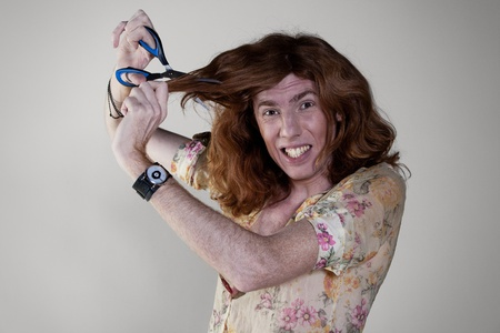 off cuts: Young man cuts off her hair with scissors and shouts