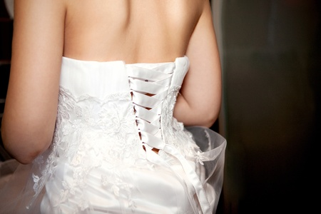 Bride being laced into a wedding dress photo