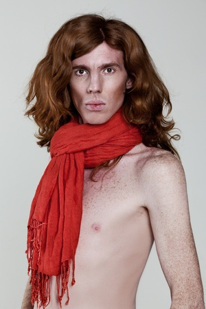 A red-haired young man with a naked torso in a red scarf photo