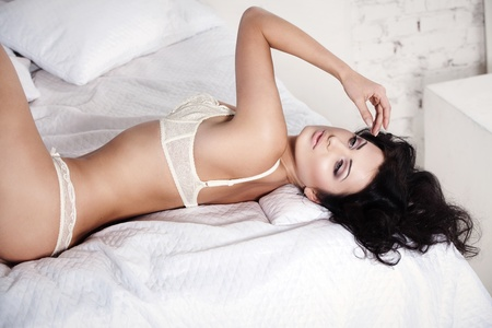 Beautiful woman in a white lingerie on the bed