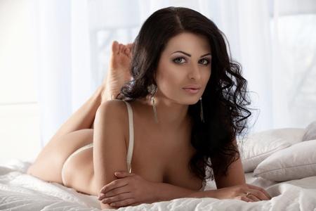 mujer en la cama: Hermosa mujer en una ropa interior blanca en la cama