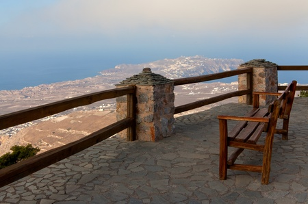 bench on the edge of the cliff overlooking the sea photo