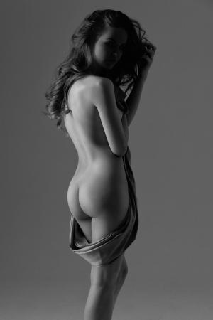femmes nues sexy: Silhouette d'une femme nue avec un chiffon satin dans ses mains Banque d'images