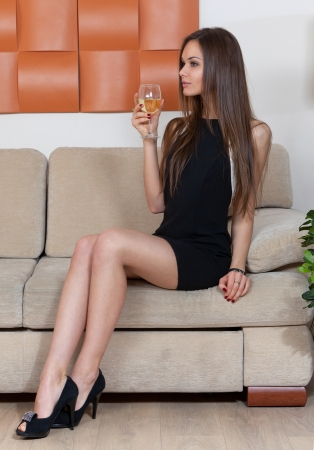 Elegant woman with a glass of wine sitting on the sofa photo