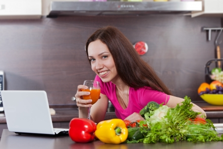 Woman drink the juice in the kitchen and looking at the computer photo