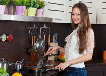 young, slender woman prepares vegetables in the kitchen