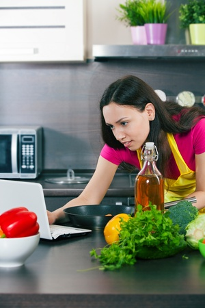 Woman prepares the food in the kitchen and looks into the computer photo