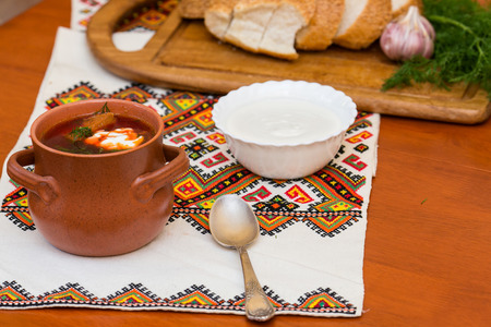 Ukrainian borsch and a bowl of sour cream on embroidered towel photo