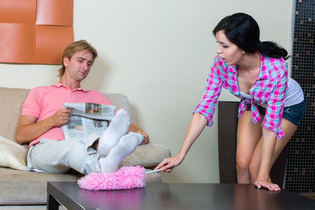 Young woman cleaning the apartment, the man reading the newspaper photo