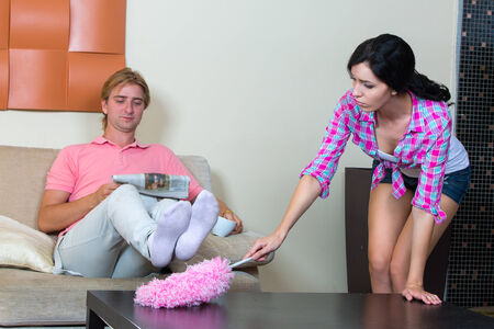 Young woman removes the apartment, the man reading the newspaper photo