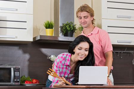 Young couple in the kitchen together cooking and look in the computer recipe photo