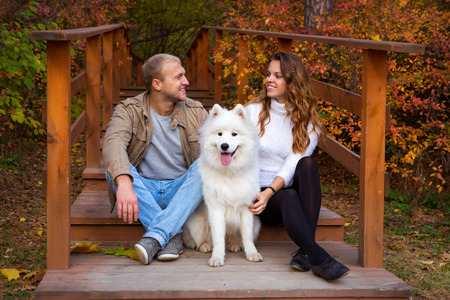 Young couple with a dog on a walk in the autumn forest photo