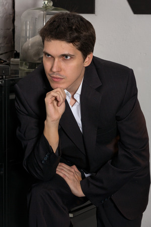 reverie: A young man in a black business suit, standing in reverie