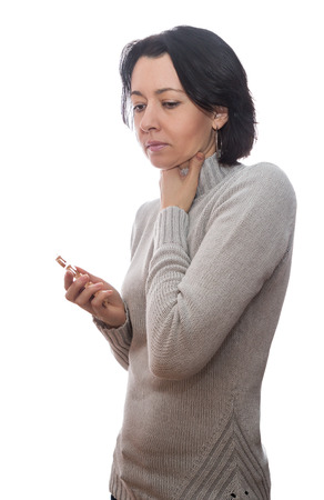 tonsillitis: Woman with a sore throat, in the hands of tablets