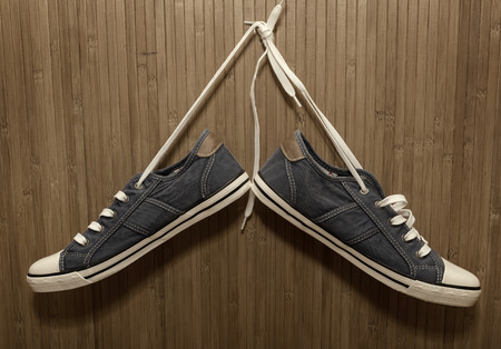 untied: New, denim sneakers hanging on a bamboo wall
