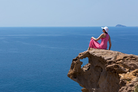 Young woman in a long striped dress and hat sitting on a rock on the sea. Greece, Santorini.