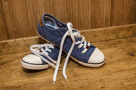untied: Canvas sneakers blue on the old wooden floor.
