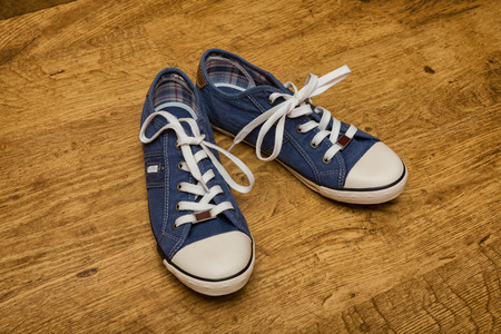 untied: Pair of blue canvas sneakers are on the yellow wood floor Stock Photo