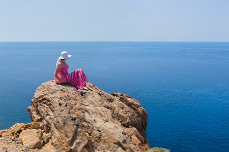 Woman in a long summer dress  sit on a cliff and watches the ships at sea. Greece, Santorini. photo