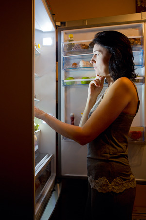 Woman in pajamas at night chooses the food in the fridge photo
