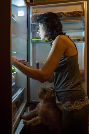 Woman and dog at night looking for food in the fridge photo